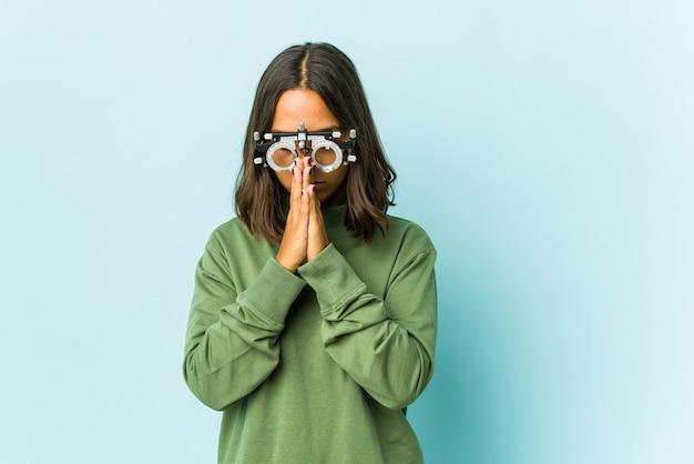 Giovane donna latina oculista che prega, che mostra devozione, persona religiosa in cerca di ispirazione divina.
