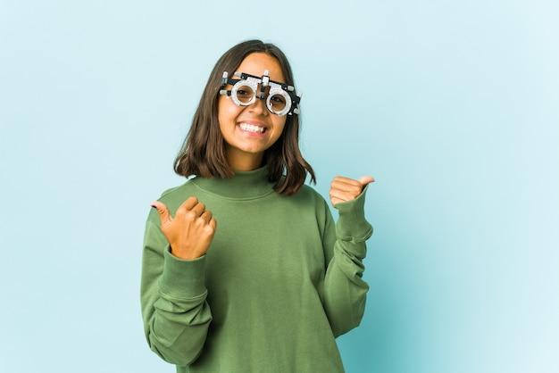 Giovane donna latina oculista che alza entrambi i pollici in su, sorridente e sicura.