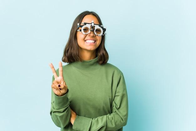 Giovane donna oculista sopra la parete isolata che mostra il numero due con le dita