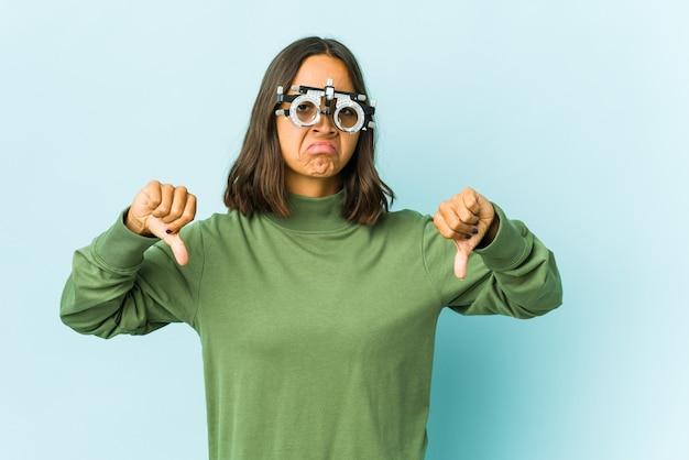 Giovane donna oculista sopra la parete isolata che mostra il pollice verso il basso, concetto di delusione