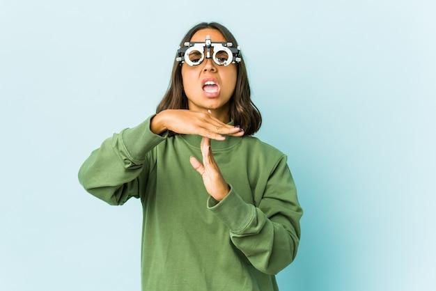Giovane donna oculista sopra la parete isolata che mostra un gesto di timeout