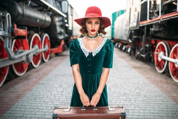 La giovane donna antiquata viaggia sul treno retrò