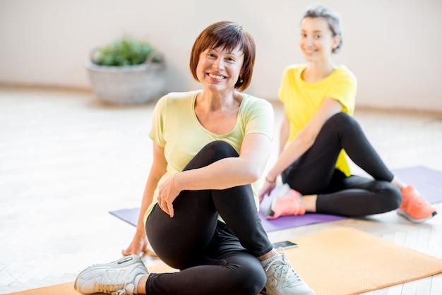 Le donne giovani e anziane in abbigliamento sportivo fanno yoga insieme al chiuso a casa o in palestra