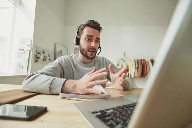 Giovane operatore con la cuffia avricolare che spiega qualcosa a uno dei clienti durante la consultazione in linea davanti al computer portatile nell'ambiente domestico
