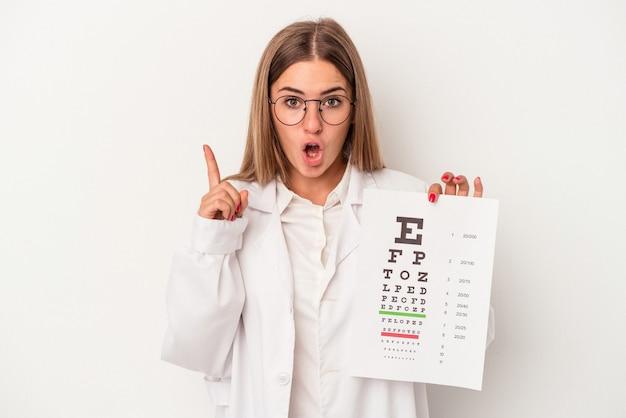 Giovane optometrista donna russa isolata su sfondo bianco con qualche grande idea, concetto di creatività.