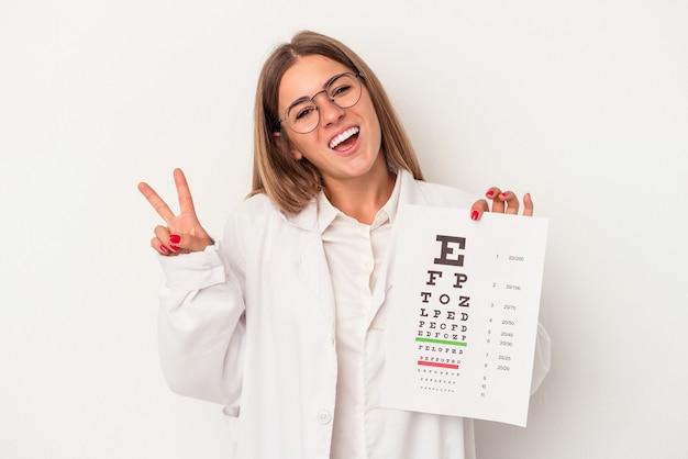 Giovane optometrista donna russa isolata su sfondo bianco gioiosa e spensierata che mostra un simbolo di pace con le dita.