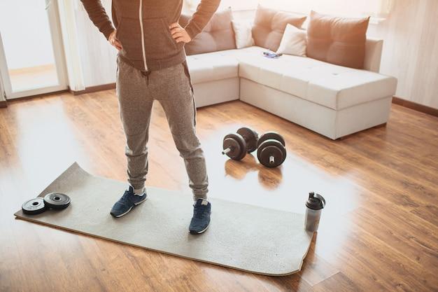 Giovane uomo ordinario che fa sport a casa. taglia la vista di un principiante o di una matricola in attività di allenamento nel suo appartamento.
