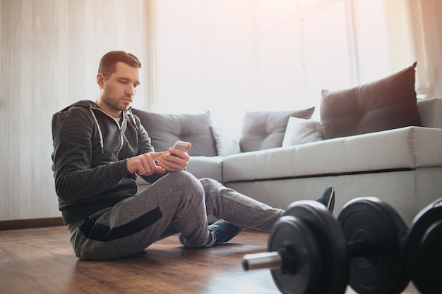 Giovane uomo ordinario che fa sport a casa. riposa seduto sul pavimento e usa lo smartphone. matricola in allenamento rilassante dopo l'allenamento. solo in appartamento. manubri sul pavimento