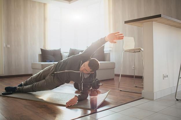 Il giovane uomo comune va a fare sport a casa. immagine luminosa del vero principiante dell'allenamento in piedi nella posizione della plancia laterale e alzare una mano. il ragazzo normale ha iniziato la sua formazione. persona laboriosa in azione.
