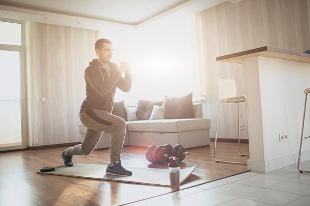 Il giovane uomo comune va a fare sport a casa. l'immagine luminosa della matricola di sport concentrata seria che fa una gamba occupa con persistenza. l'uomo regolare lavora sulla forma del suo corpo per migliorare.