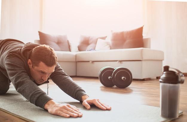 Il giovane uomo comune va a fare sport a casa. taglia la vista del ragazzo principiante che allunga il suo corpo e tira le mani avanti sul tappeto. migliorare la forma del corpo. un vero uomo senza conoscenza dello sport inizia l'allenamento.