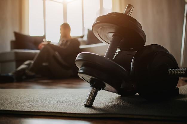 Il giovane uomo comune va a fare sport a casa. la vista scura sul preson maschio stanco dopo l'addestramento si siede sul pavimento e riposa. ragazzo normale dopo l'esercizio. manubri scuri davanti all'immagine.