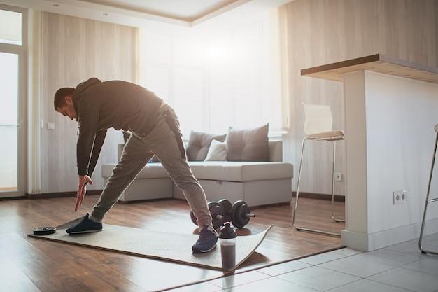 Il giovane uomo comune va a fare sport a casa. ragazzo che si dimenava sulla forma del suo corpo per stare meglio. principiante nello sport allungando la cravatta con entrambe le mani. allenarsi da solo in appartamento. concentrato persistente.