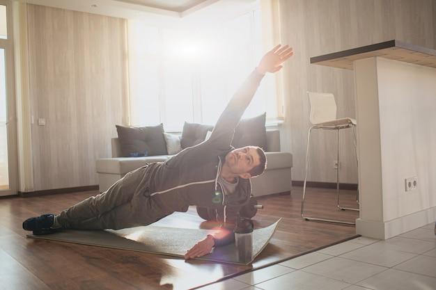 Il giovane uomo comune va a fare sport a casa. il principiante persistente di allenamento della matricola sta nella posizione dell'asse laterale e guarda su sulla sua mano allungata. esercizio da solo in appartamento. ragazzo normale nella foto.