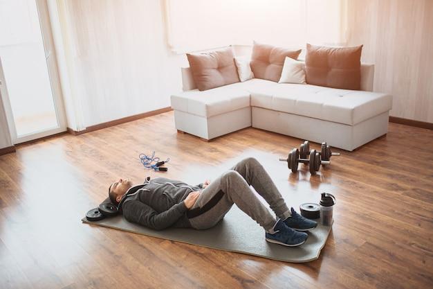 Il giovane uomo comune va a fare sport a casa. principiante abituale sdraiato sul tappetino sul pavimento e ha riposo. immagine reale di un ragazzo con un corpo normale. perdere peso o cercare di mantenersi in forma.