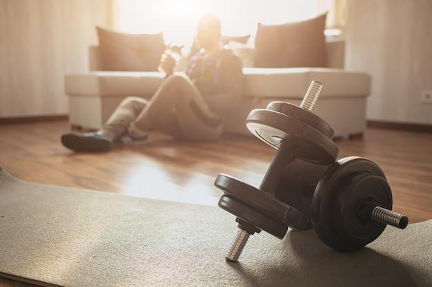 Il giovane uomo comune va a fare sport a casa. il ragazzo normale si siede sul divano sul pavimento dopo un duro allenamento. riposa e beve acqua. sfondo sfocato soleggiato. coppia di manubri sdraiato sul tappeto davanti.