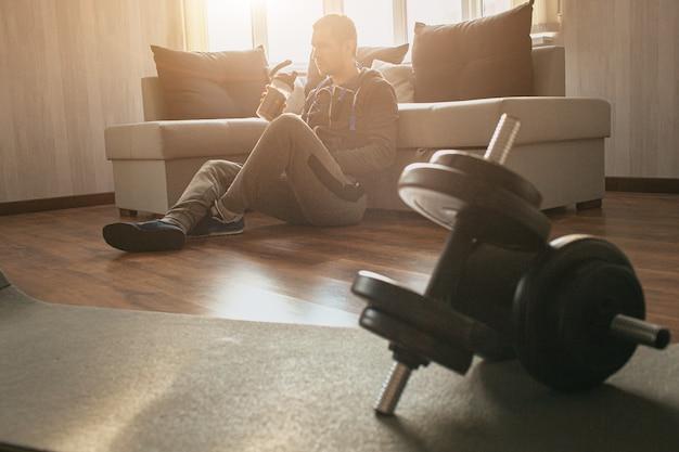 Il giovane uomo comune va a fare sport a casa. la matricola stanca di allenamento si siede sul pavimento da sola e ha riposo dopo l'esercizio. bevi acqua e rilassati. coppia di manubri sdraiato sul tappeto. uomo normale dopo l'allenamento.
