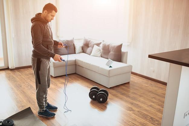 Il giovane uomo comune va a fare sport a casa. la matricola di worksout o la corda da salto per amatore tengono entrambe le mani e sono pronte per l'uso. l'uomo normale lavora sulla sua forma fisica. miglioramento continuo.