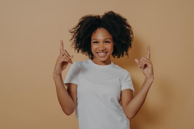 Giovane donna dalla pelle scura felicissima che punta verso l'alto con gli indici, isolata su sfondo beige