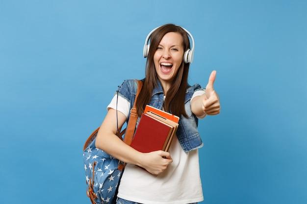Giovane studentessa felicissima in abiti in denim con zaino, cuffie che ascoltano musica in possesso di libri scolastici che mostrano pollice in su isolato su sfondo blu. istruzione al college universitario di scuola superiore.