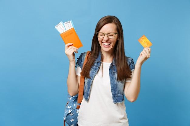 Giovane studentessa felicissima con lo zaino con gli occhi chiusi che tengono i biglietti della carta d'imbarco del passaporto, carta di credito isolata su fondo blu. istruzione in college universitario all'estero. volo aereo.