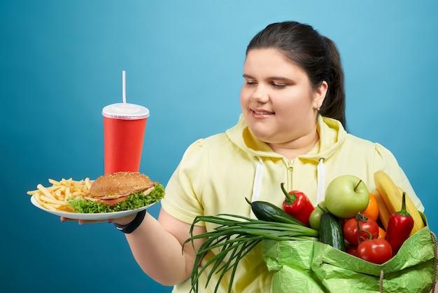 Giovane donna felice oversize guardando il piatto con fast food mantenendo frutta e verdura fresca sulla sua mano. la ragazza carina sta scegliendo tra mangiare sano e fast food