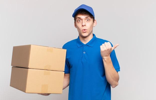 Il giovane pacco consegna un ragazzo che sembra stupito per l'incredulità, indicando l'oggetto sul lato e dicendo wow, incredibile
