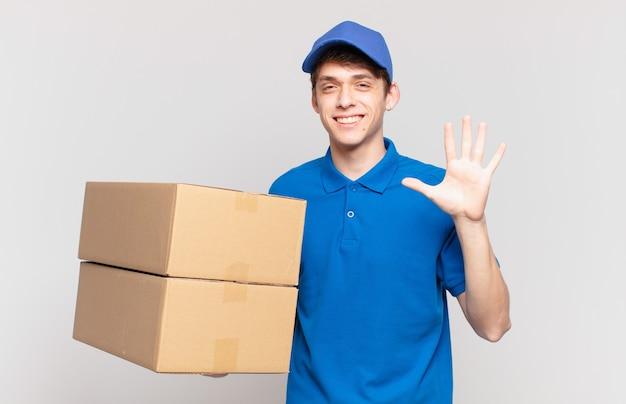 Il pacchetto giovane consegna un ragazzo sorridente e dall'aspetto amichevole, mostrando il numero cinque o il quinto con la mano in avanti, conto alla rovescia