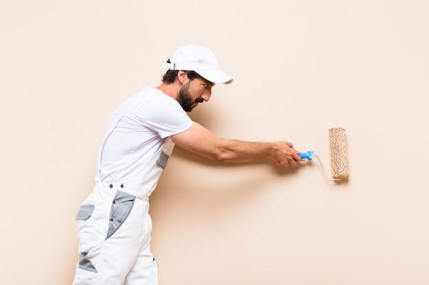 Uomo barbuto del giovane pittore che vernicia un muro con un rullo di vernice