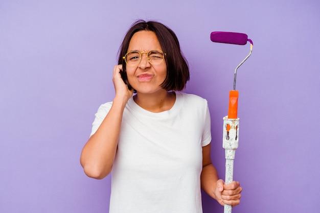 Giovane pittore di razza mista donna in possesso di un bastoncino di vernice isolato su sfondo viola che copre le orecchie con le mani.