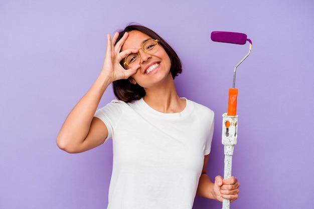 La donna della corsa mista del giovane pittore che tiene un bastone della vernice isolato su fondo viola eccitato mantenendo il gesto giusto sull'occhio.