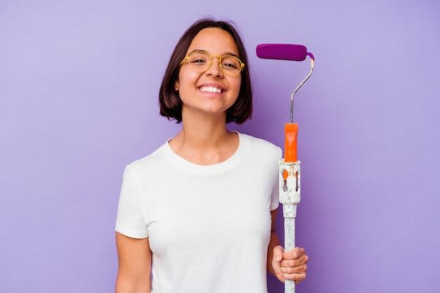 Giovane pittore di razza mista donna in possesso di un bastoncino di vernice isolato su sfondo viola felice, sorridente e allegro.