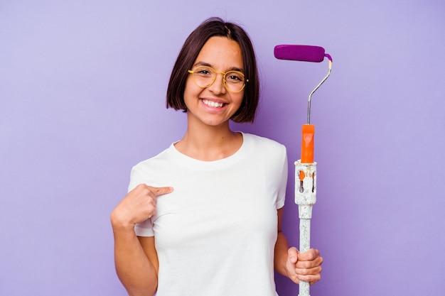 Giovane pittore di razza mista donna che tiene un bastoncino di vernice isolato su sfondo viola persona che punta a mano uno spazio di copia della camicia, orgoglioso e fiducioso