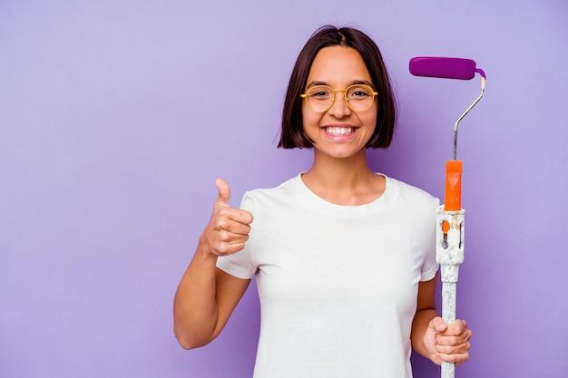 Donna di razza mista giovane pittore che tiene un bastoncino di vernice isolato su sfondo viola sorridendo e alzando il pollice