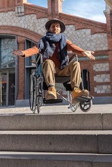 Giovane latinoamericano paralizzato su una sedia a rotelle per strada che indossa un cappello frustrato e indignato davanti ad alcune scale che non può scendere