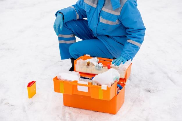 Giovane paramedico in abbigliamento da lavoro blu e guanti che controllano la medicina e gli articoli di pronto soccorso in kit all'aperto
