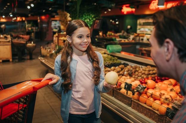 Giovane genitore e figlia in drogheria. tiene in mano la mela e il carrello. ragazza guarda padre e sorriso. sorriso uomo.