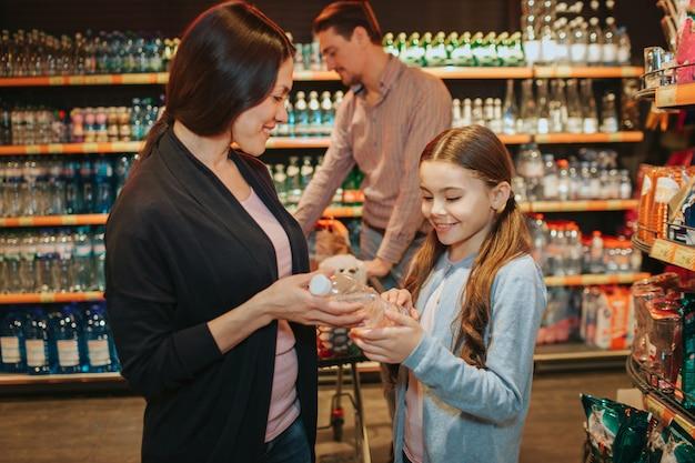 Giovani genitori e figlia in drogheria. la donna e il bambino tengono insieme la bottiglia di acqua. padre in piedi dietro con carrello della spesa.