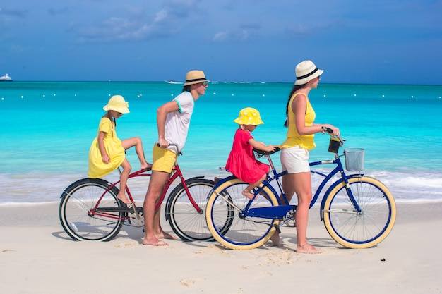 Giovani genitori e bambini in sella a biciclette su una spiaggia di sabbia bianca tropicale