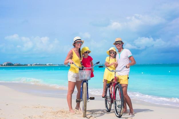 Giovani genitori e bambini che guidano le biciclette su una spiaggia di sabbia bianca tropicale