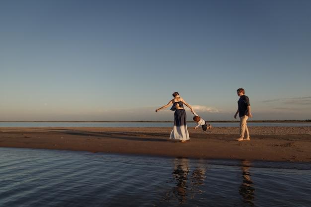 Giovani genitori che giocano con il loro bambino sulla spiaggia in riva al mare.