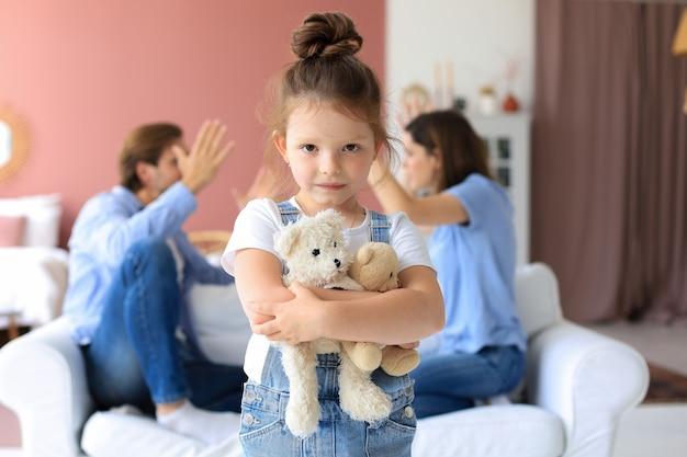Giovani genitori seduti uno di fronte all'altro sul divano imprecando ad alta voce e gesticolando con le mani mentre la piccola figlia indifesa è sconvolta guardando la fotocamera.