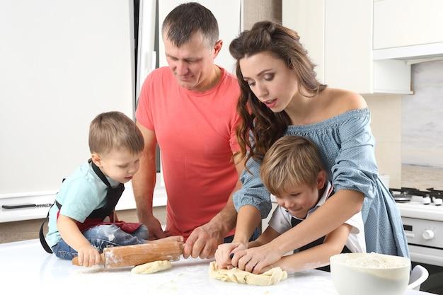Giovani genitori accanto a bambini piccoli che impastano la pasta sul tavolo della cucina