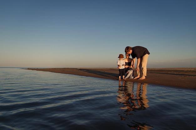 I giovani genitori trascorrono del tempo con il loro bambino sulla spiaggia in riva al mare bellissimo riflesso nell'acqua