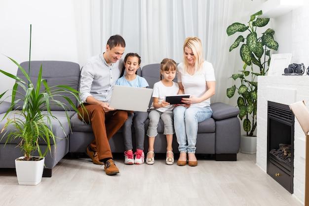 Giovani genitori, con bambini, al computer portatile