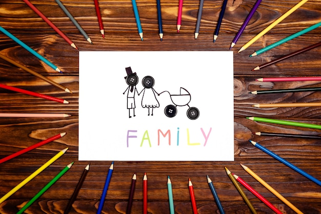 Giovani genitori con un passeggino su un tavolo di legno. il concetto di famiglia. la vista dall'alto