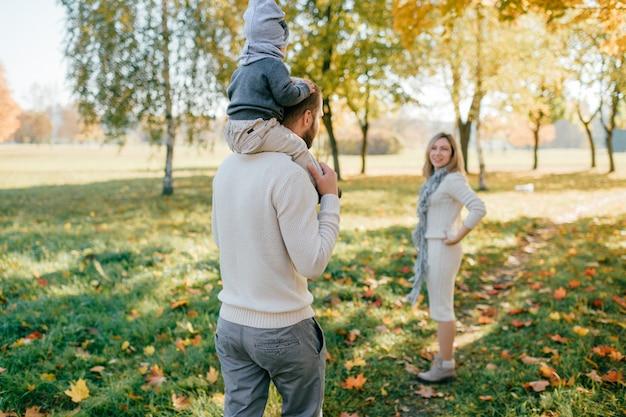 Giovani genitori con il loro bambino che trascorrono del tempo in autunno parco.