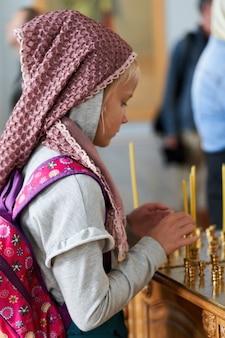 Un giovane parrocchiano accende una candela all'altare della chiesa. ragazza credente con le candele in chiesa