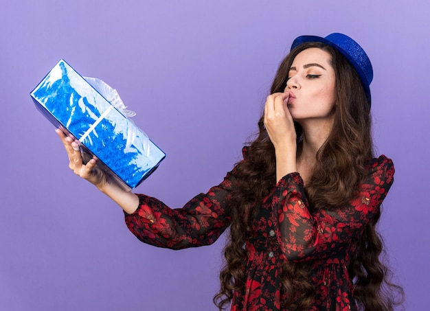 Giovane ragazza che indossa un cappello da festa in piedi nella vista di profilo tenendo e guardando il pacchetto regalo facendo il gesto del bacio dello chef isolato sul muro viola