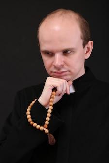 Giovane pastore con rosario in legno, isolato sul nero